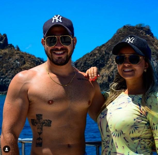 Na foto, aparece Caio sem camisa ao lado de sua esposa que está com uma camisa com estampa com bananas.