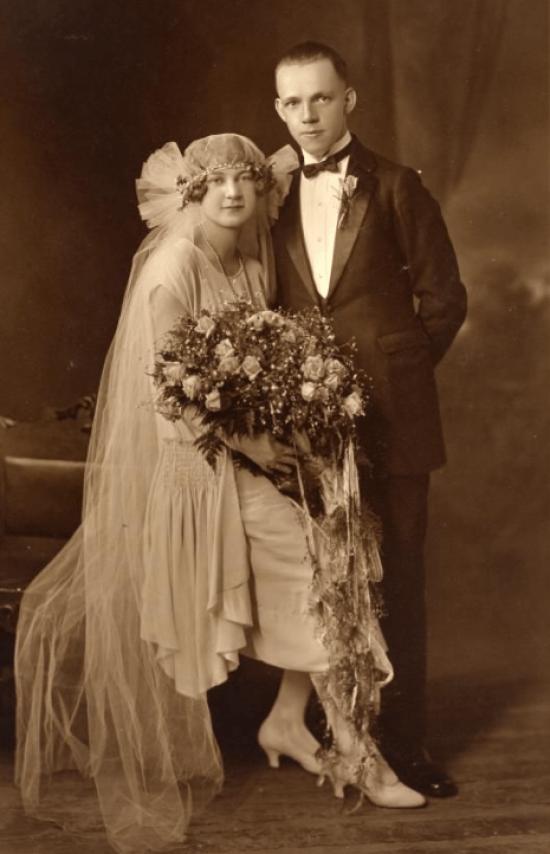 Noiva sentada e noivo em pé em foto de casamento de 1920