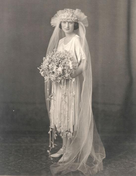 Noiva com vestido, chapéu, véu e buquê típicos de 1920.