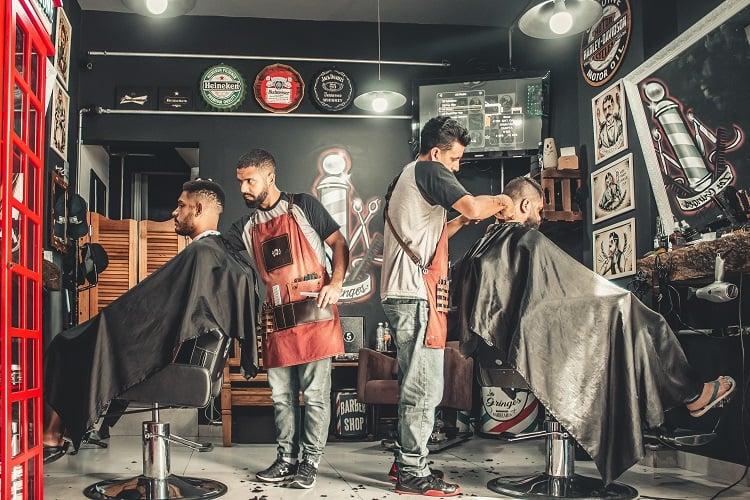 dois homens cortando o cabelo em uma barbearia