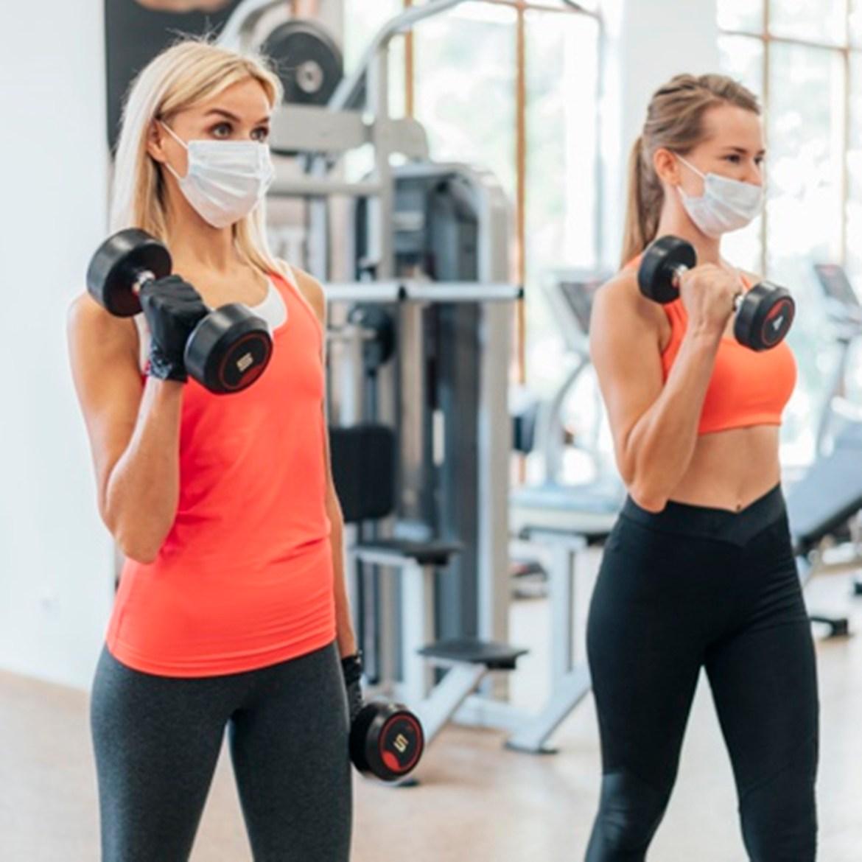 Mulheres malhando na academia e usando máscaras faciais.
