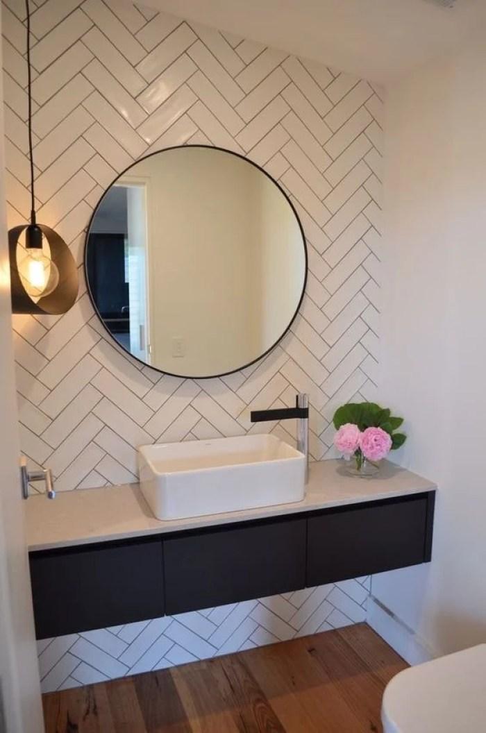 Banheiro minimalista com espelho redondo