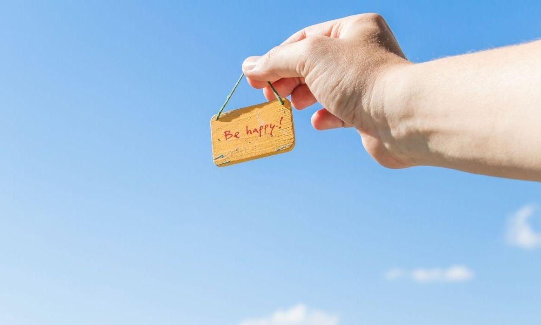 """mão apontando para frase """"be happy"""" - vender milhas"""