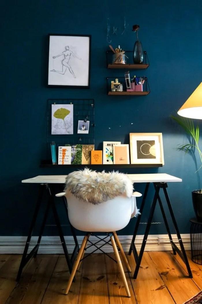Parede azul marinho e mesa branca.