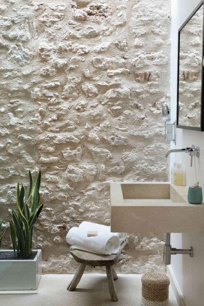 Banheiro com parede branca de pedra.