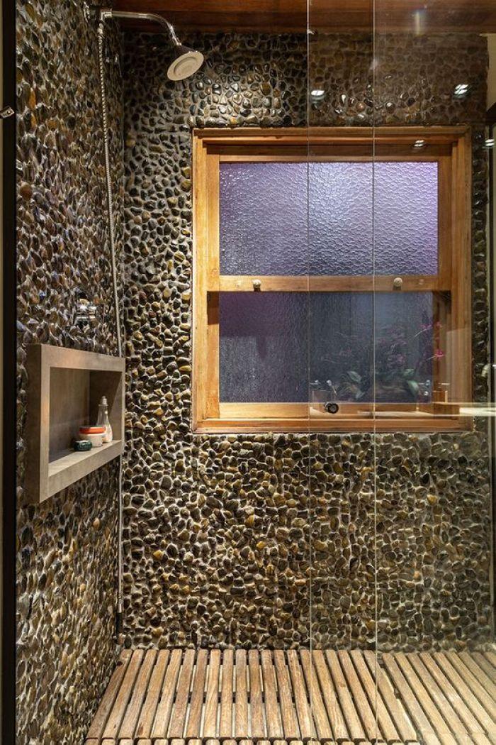 Box de chuveiro com pedras e madeira.