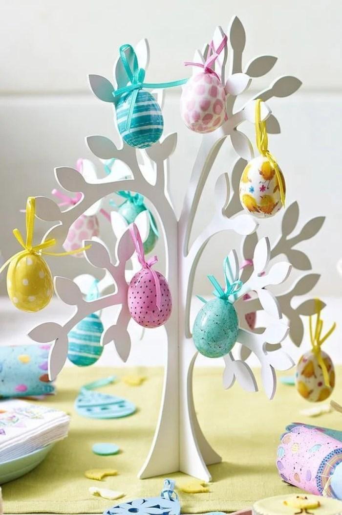 Árvore de MDF com ovos pendurados.