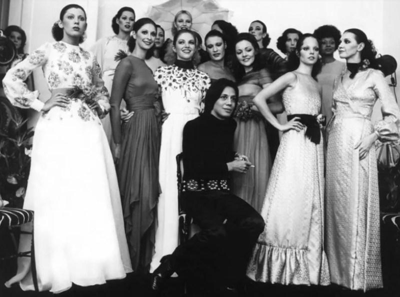 Clodovil Hernandes com modelos em um desfile de 78, com Elke Maravilha no fundo.