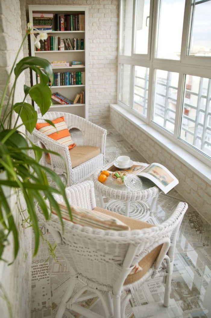 Duas cadeiras e mesa na varanda.
