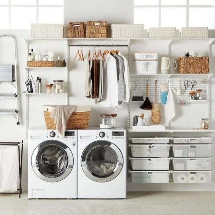 Lavanderia com duas máquinas de lavar com potes e cestos que garantem a organização.
