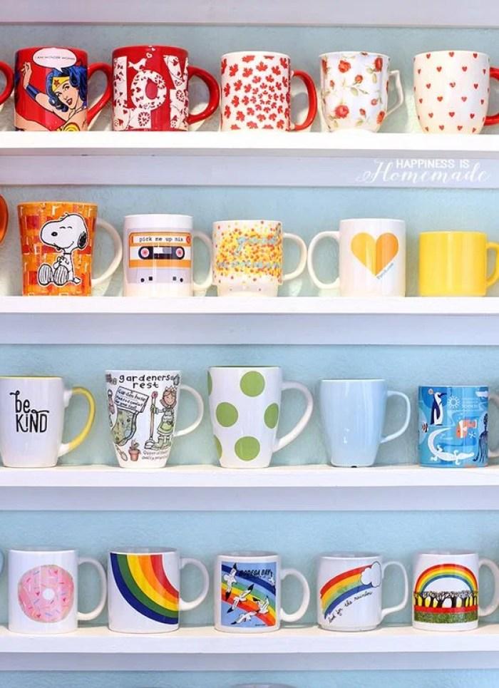 Organização de prateleiras com canecas coloridas separadas por cor.