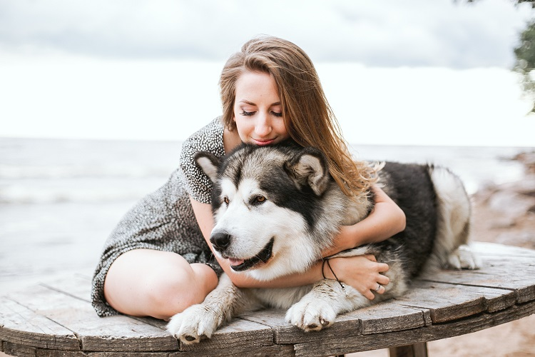 mulher abraçando cachorro