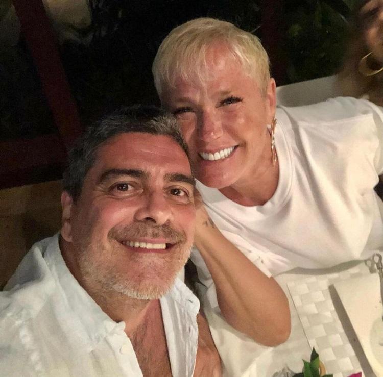 Junno e Xuxa aparecem sorrindo, juntinhos
