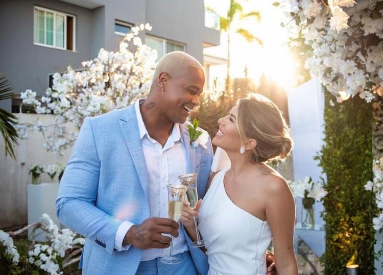 Leo Santana e Lorena Improta brindando, com taças de champagne nas mãos, durante o casamento