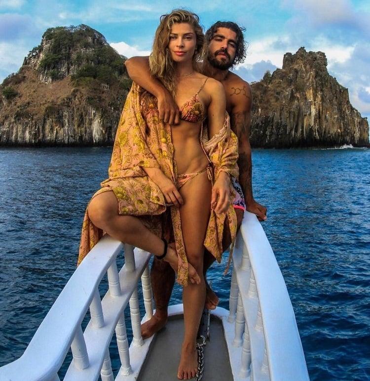 Grazi Massafera e Caio Castro posam em um barco, com roupas de praia, em Fernando de Noronha
