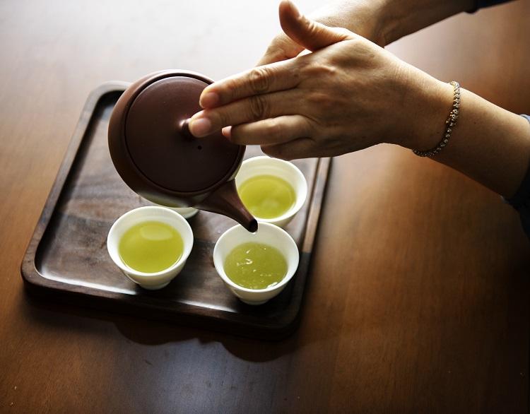 mulher colocando chá de bule em xícaras