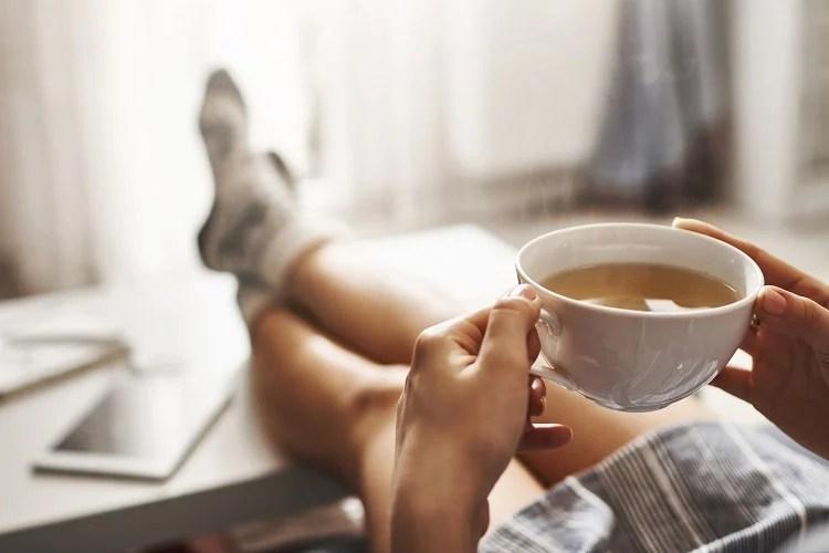 mulher tomando xícara de chá de alface