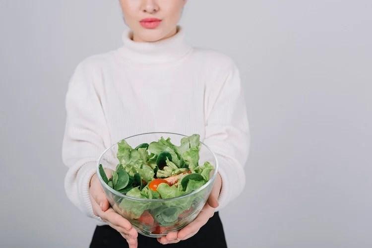 mulher segurando tigela de vidro com salada verde