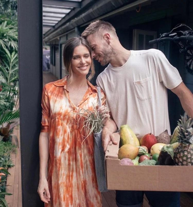Sorrindo, Fernanda Lima e Rodrigo Hilbert posam com frutas, legumes e verduras