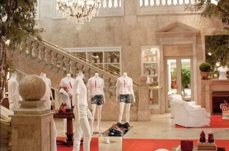 """Foto de um salão da Daslu com cartazes dizendo """"Sales""""."""