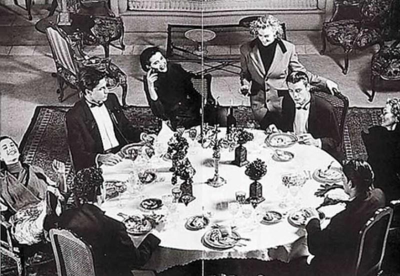 Foto em preto e branco de várias pessoas ao redor de uma mesa redonda na Sala de Importados da Daslu.