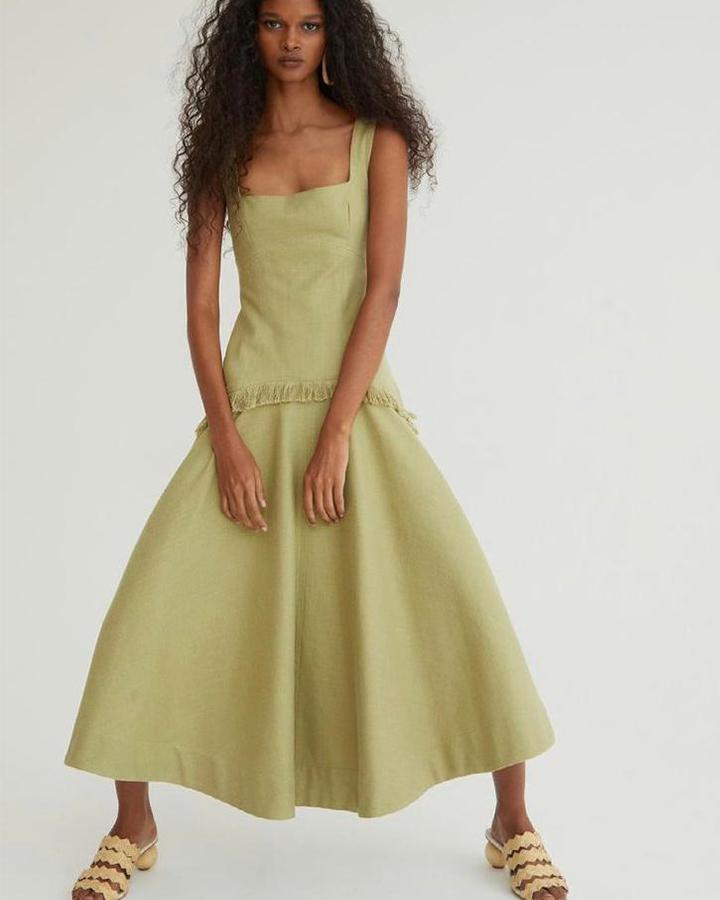 Modelo usando um vestido verde longo.