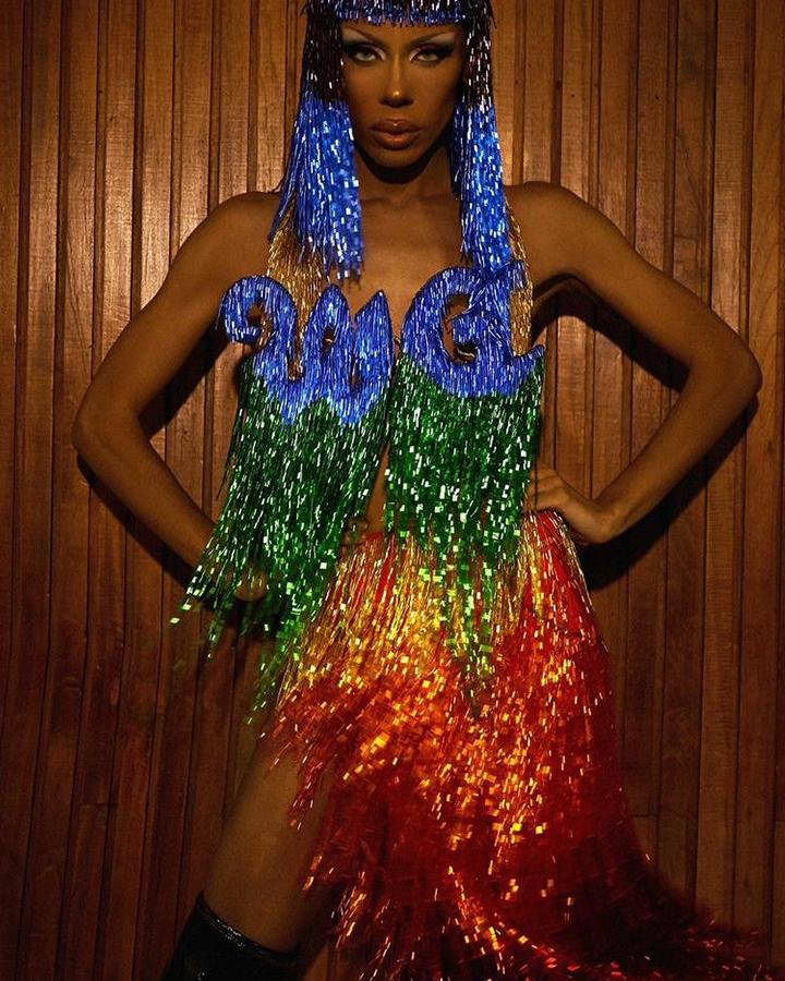 Modelo com vestido com as cores do arco-íris e um W.A. azul cobrindo o peito.
