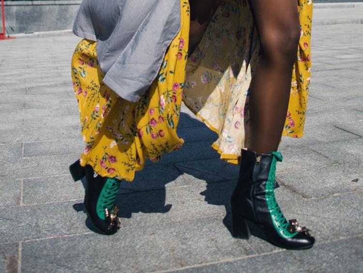Mulher posando pra foto usando botas, vestido amarelo e cardigã longo.