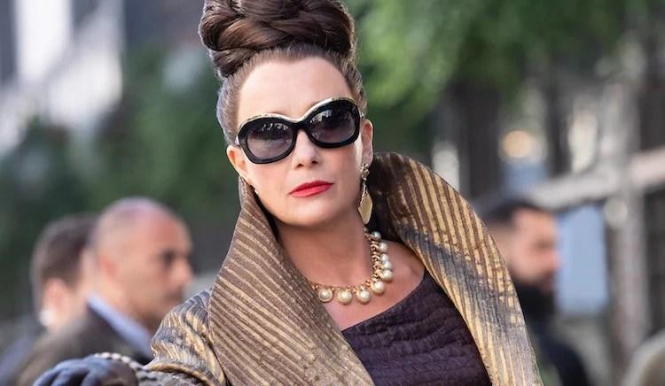 Baronesa Von Hellman usa óculos escuros, batom vermelho vivo e um modelo dourado