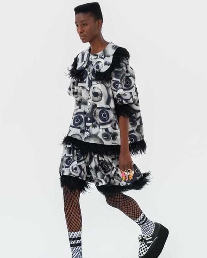 Modelo desfilando um conjunto com estampa de olhos e babados pretos.