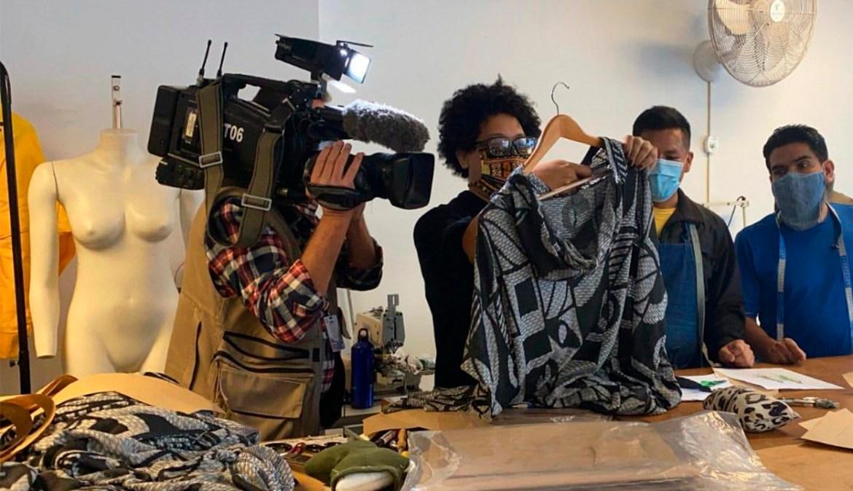 Estilista Isaac Silva é filmado enquanto segura uma de suas criações na mão.