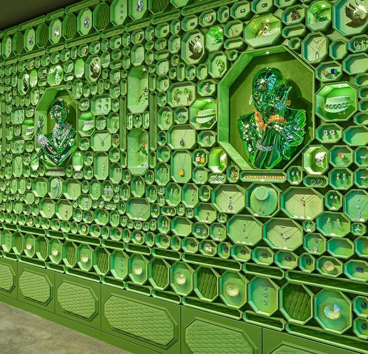 Layout da parede da loja nova da Swarovski. Cheia de texturas e formatos, tudo em verde.