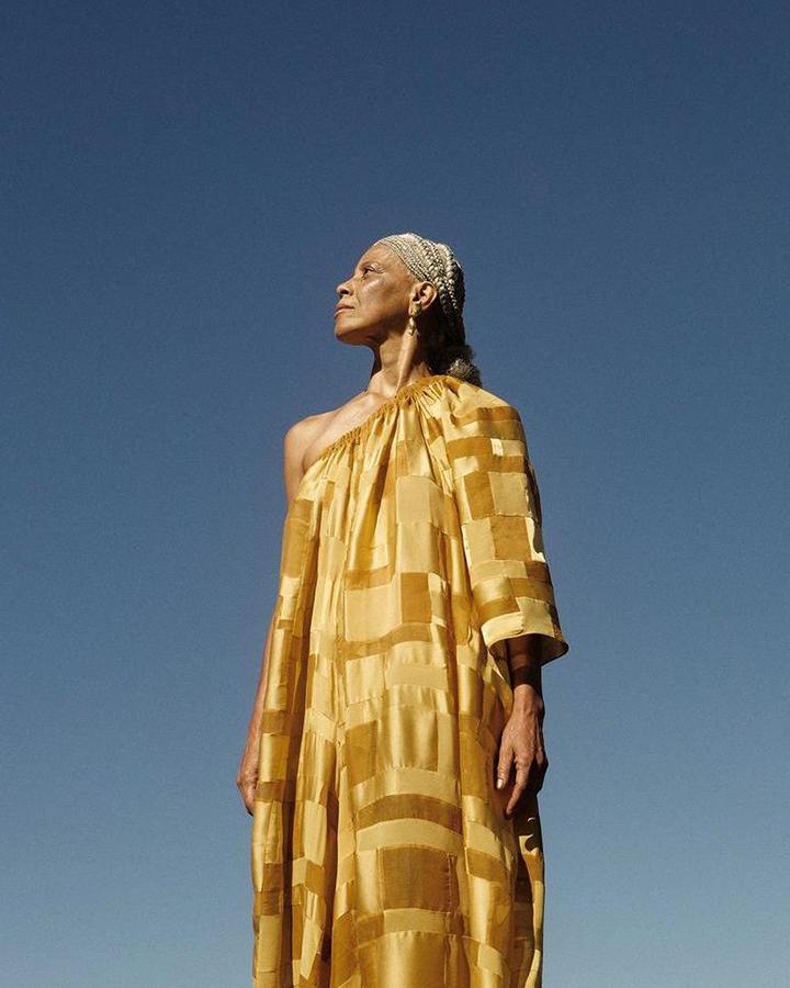 Modelo usa um vestido amarelo longo.
