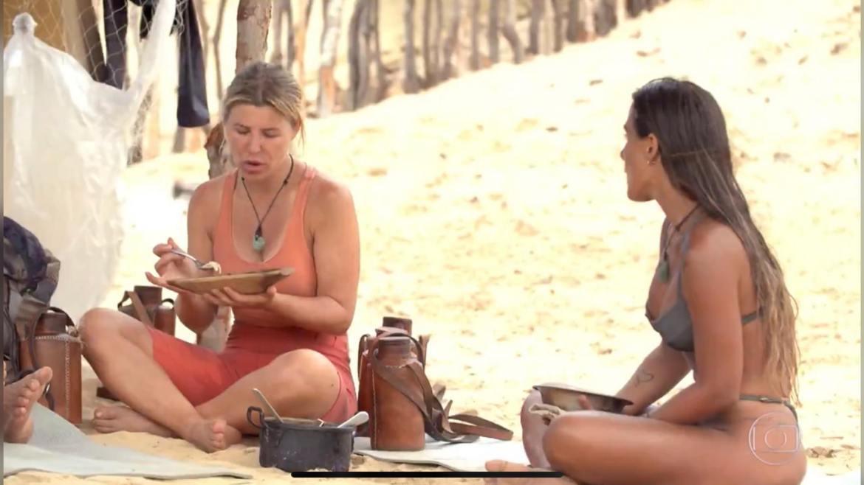 Carol Peixinho ouve as fofocas de Íris sobre a tribo Carcará (imagem: reprodução/ Globo)