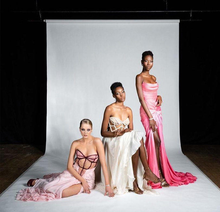 Três modelos com vestidos rosa claro, branco e rosa choque.