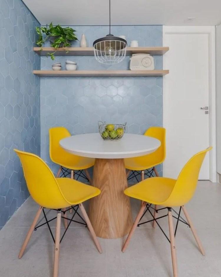 Parede azul e cadeiras amarelas.