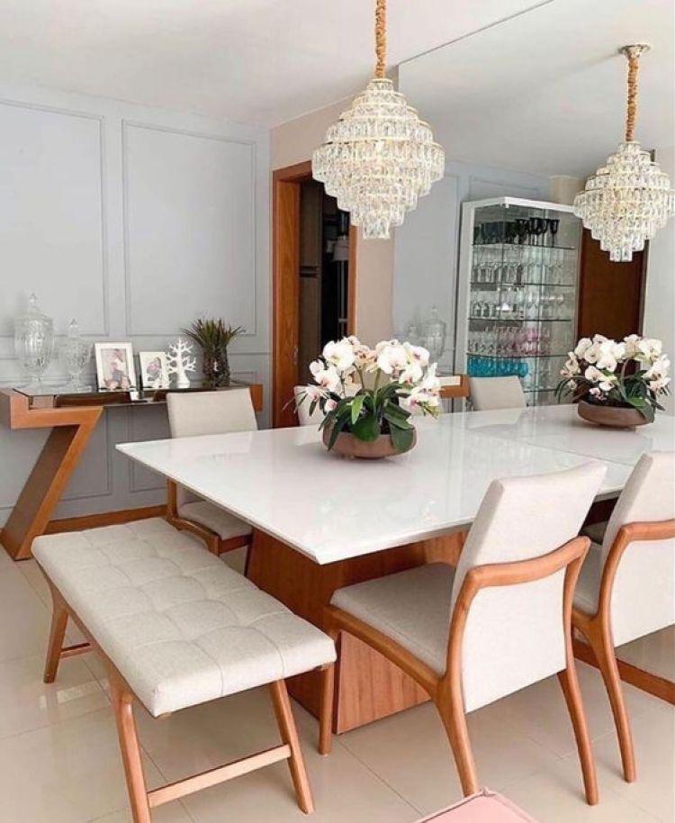 Sala de jantar com lustre e aparador.