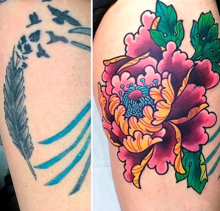 Tatuagem de uma pena azul e pássaros. Ela foi coberta por outra tatuagem, maior, de uma flor colorida.