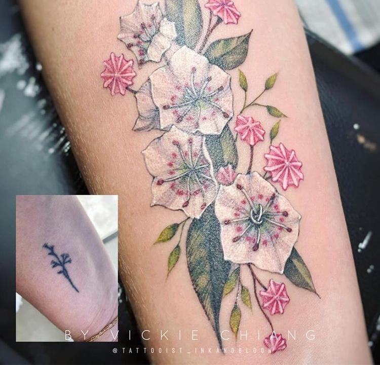 Tatuagem de flores coloridas cobre uma antiga e menor de flores pretas.