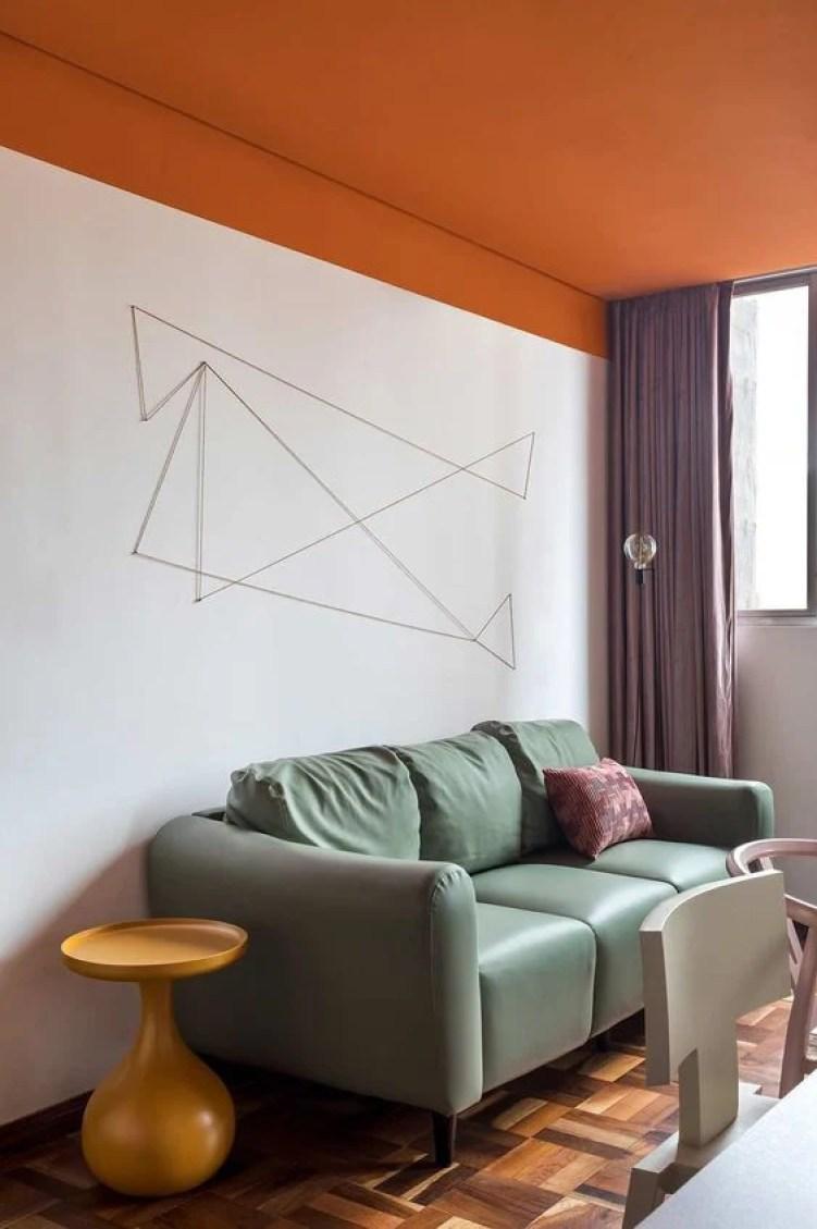 Teto laranja e sofá cinza.