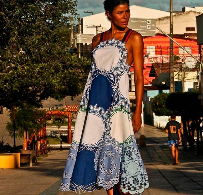 Modelo com Vestido longo azul e branco.