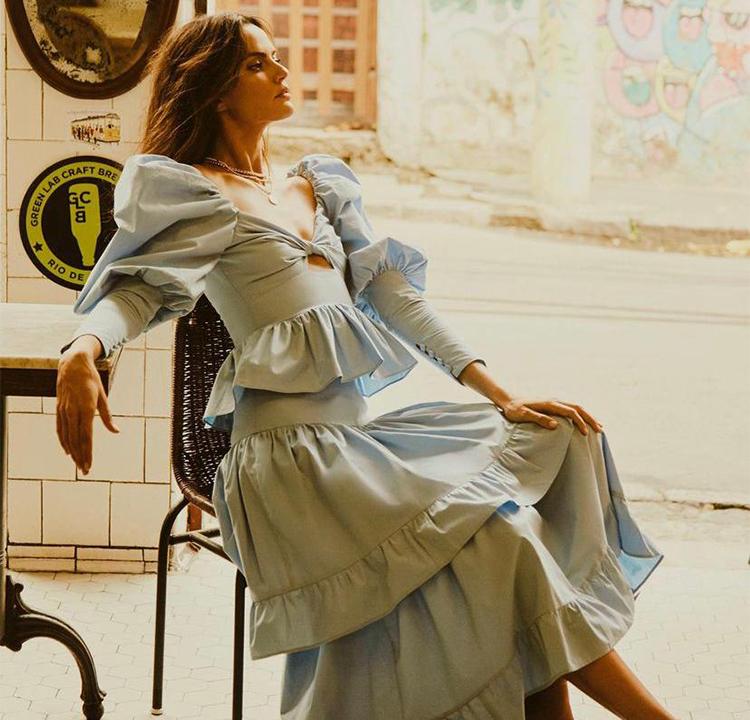 Modelo senta em cadeira e usa um vestido azul claro longo com mangas.