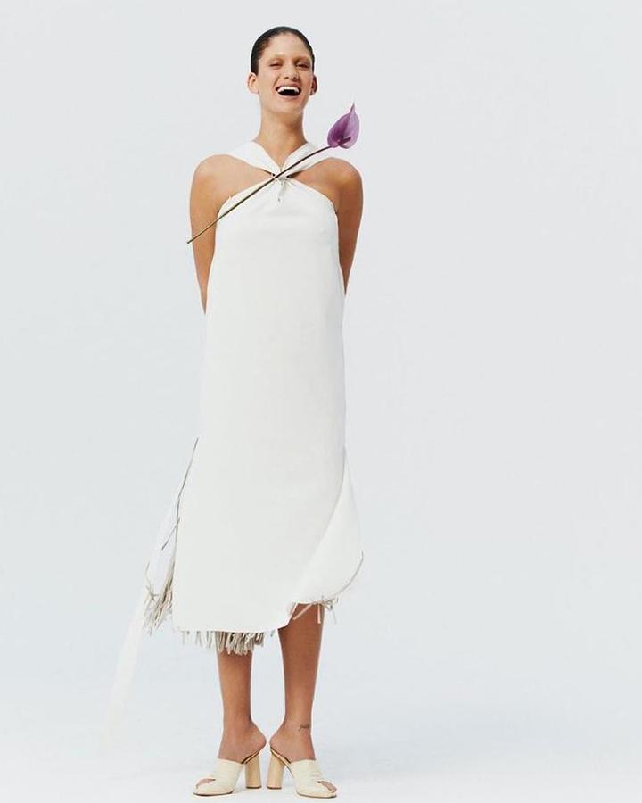 Modelo usa vestido branco sem mangas com flor roxa.