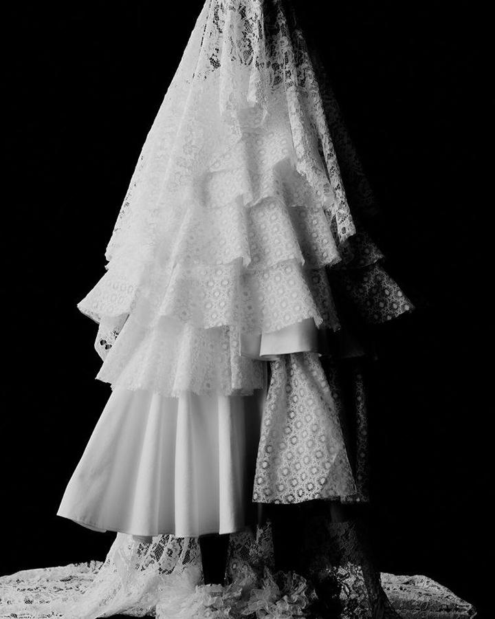Vestido branco de renda com véu de renda. Foto em preto e branco.