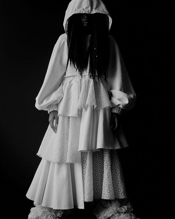 Vestido branco com capuz. Foto em preto e branco.