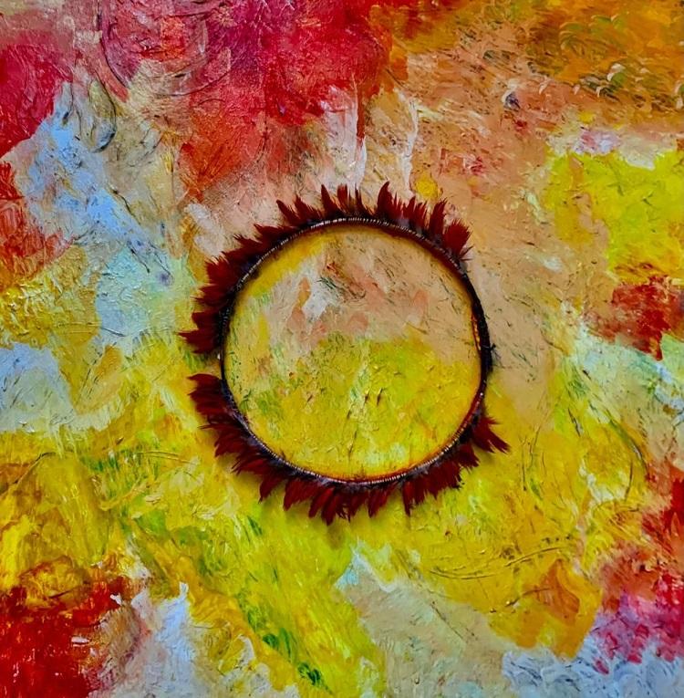 Obra de arte abstrata em tons de vermelho, amarelo e branco, com cocar de penas no centro