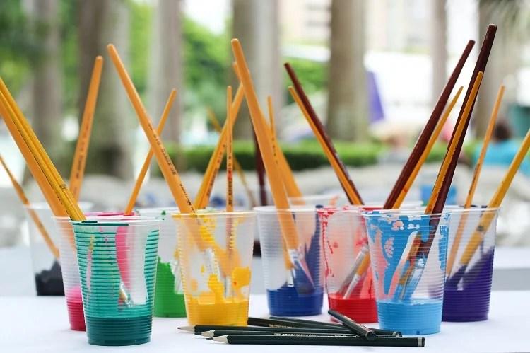 Foto de vários copos de plástico com tinta colorida e pincel dentro