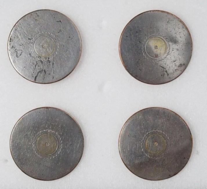 Foto de 4 botões feito em metal liso e achatado com estampa floral no centro sobre fundo branco
