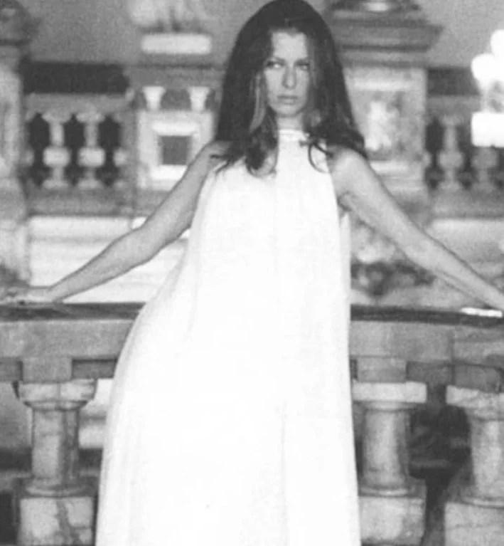 """Imagem em preto e branco de Danuza Leão em uma cena do filme """"Terra em Transe"""" posando com um vestido branco solto de Guilherme Guimarães"""