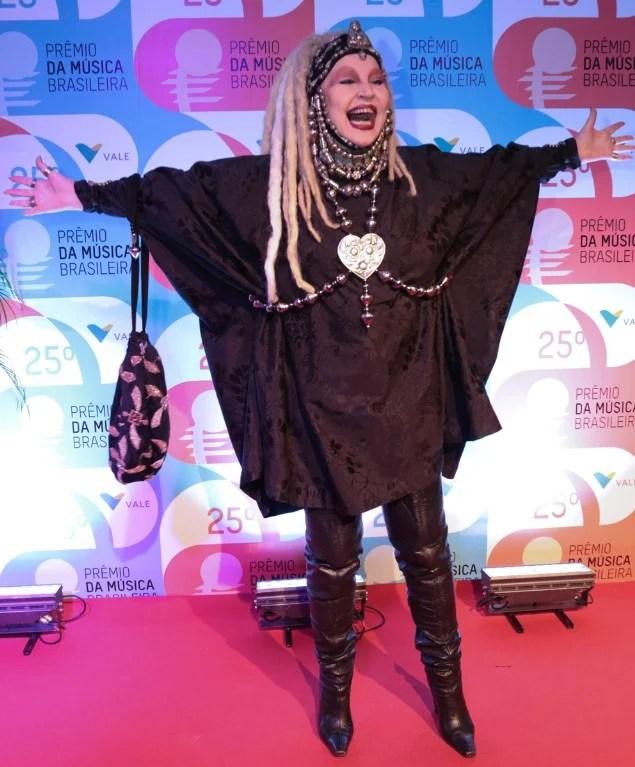 Elke Maravilha posando sorrindo no 25º Prêmio da Música Brasileira em pé e de braços abertos, vestida toda de preto, com botas de cano alto, peruca loira estilo dreadlocks e muitos acessórios.